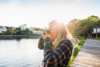 Woman taking photographs on waterfront at Granville Island, Vancouver, Canada