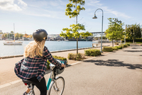 Woman cycling along waterfront, Vancouver, Canada