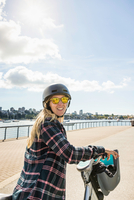 Portrait of woman on bicycle at waterfront, Vancouver, Canada