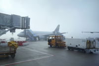 Refuelling truck and airplane on airport apron in mist