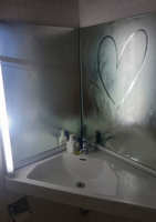 Heart drawn on steamy bathroom mirror