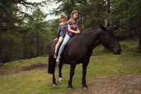 Girl and woman sitting bareback on horse in forest glade, Sattelbergalm, Tyrol, Austria 11015298694| 写真素材・ストックフォト・画像・イラスト素材|アマナイメージズ