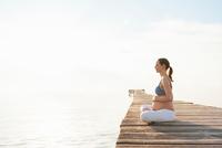 Pregnant woman sitting cross legged on pier meditating, Majorca, Spain