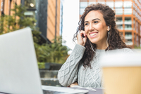 Mid adult woman, sitting outdoors, wearing earphones, using laptop for video call
