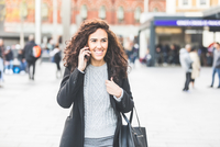 Mid adult woman, walking outdoors, using smartphone, smiling