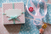 Overhead view of gift box, ribbon and paper flowers