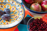 Tree bowls with red apples, plums and berries