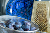 Plums in sieve and grater