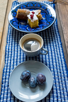 Table with bowl of cake, black coffee and plums 11015298806| 写真素材・ストックフォト・画像・イラスト素材|アマナイメージズ