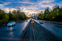Wet highway and tramline at sunset
