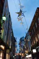 Star shape christmas decorations above city street at dusk, London, UK