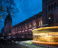 Illuminated spinning carousel by Natural History Museum at dusk, London, UK