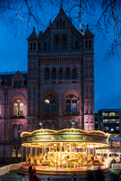 Illuminated carousel by Natural History Museum at dusk, London, UK