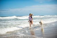 Young girl running through sea with dog 11015299051| 写真素材・ストックフォト・画像・イラスト素材|アマナイメージズ