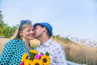 Couple holding flowers, kissing on cheek