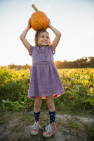 Portrait of young girl, holding pumpkin on head