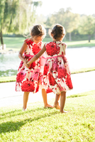 Two young girls dancing together on grass, rear view