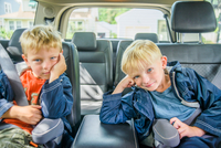 Twin brothers sitting in back of vehicle, bored expressions