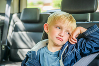 Young boy sitting in back of vehicle, bored expression