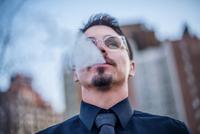 Young man outdoors, exhaling smoke