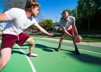 Two men playing basketball on outdoor court
