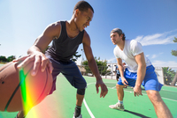 Two male friends playing basketball on outdoor court