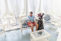 Senior male golfer sitting in conservatory with golf bag
