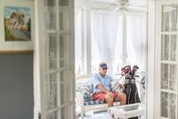 Senior male golfer sitting through conservatory doorway with golf bag 11015300204| 写真素材・ストックフォト・画像・イラスト素材|アマナイメージズ
