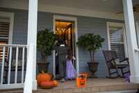 Brother and sister trick or treating at neighbour's front door