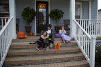 Brother and sisters trick or treating on porch stairway
