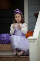 Girl trick or treating in fairy costume sitting on stairway drinking lemonade