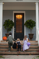 Rear view of boy and sisters trick or treating moving up porch stairway