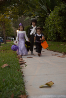Boy and sisters trick or treating walking on sidewalk 11015300548| 写真素材・ストックフォト・画像・イラスト素材|アマナイメージズ