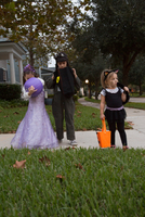 Boy and sisters trick or treating looking in bags on sidewalk 11015300550| 写真素材・ストックフォト・画像・イラスト素材|アマナイメージズ