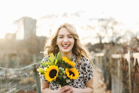 Portrait of young woman holding sunflowers, smiling