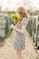 Young woman holding sunflowers, side view