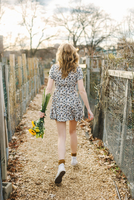 Young woman walking outdoors, holding sunflowers, rear view 11015300666| 写真素材・ストックフォト・画像・イラスト素材|アマナイメージズ