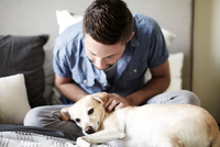 Young man petting dog on bed