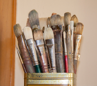 Paintbrushes in tin metal can