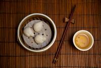 Asian dumplings, tea and chopsticks on bamboo mat