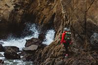 Hiker climbing over rocks, Big Sur, California, USA