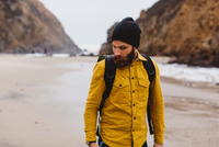 Hiker walking on beach, Big Sur, California, USA