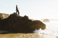 Diver with speargun standing on rock, Big Sur,  California, USA