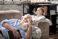 Baby girl touching sleeping grandfather on couch
