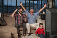 Three generation family watching television at home
