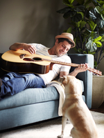 Cool mid adult man playing acoustic guitar on sofa, watched by dog 11015301466| 写真素材・ストックフォト・画像・イラスト素材|アマナイメージズ