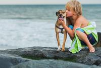 Young boy crouching on rocks at beach, hugging pet dog 11015301481| 写真素材・ストックフォト・画像・イラスト素材|アマナイメージズ