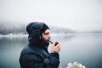 Side view of man smoking pipe by lake, Bass Lake, California, USA