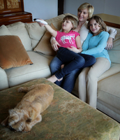 Mother and daughters sitting on sofa, watching TV together 11015301854| 写真素材・ストックフォト・画像・イラスト素材|アマナイメージズ