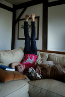 Young girl lying on sofa with pet dog, legs in the air 11015301858| 写真素材・ストックフォト・画像・イラスト素材|アマナイメージズ